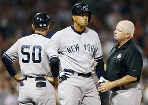 Photo - The Yankees' Alex Rodriguez, center, is tended to by a trainer at first base after being hit by a pitch in the second inning Sunday. Rodriguez got hit by a fastball from Boston starter Ryan Dempster. AP Photo