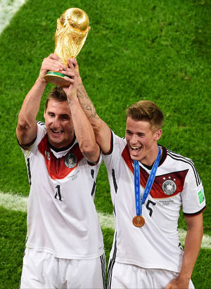 Photo - Germany's Miroslav Klose holds up the trophy next to Germany's Erik Durm after the World Cup final soccer match between Germany and Argentina at the Maracana Stadium in Rio de Janeiro, Brazil, Sunday, July 13, 2014. Mario Goetze volleyed in the winning goal in extra time to give Germany its fourth World Cup title with a 1-0 victory over Argentina on Sunday. (AP Photo/Francois Xavier Marit, Pool)