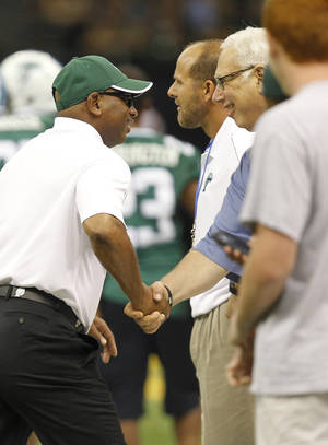 Photo -   Getting ready for his first game as head football coach at Tulane, Curtis Johnson, center, shakes hands with Tulane president Scott Cowen, before the start of their game against Rutgers at the Mercedes Benz Superdome in New Orleans on Saturday, Sept. 1, 2012. (AP Photo/The Times-Picayune, Chris Granger)