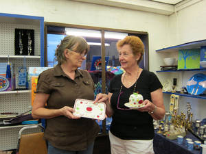 Photo - At the Emanuel Synagogue gift shop Tuesday, Brenda Hooper of Edmond and Francis Marwil of Oklahoma City discuss a platter and hot pot designed for use during Rosh Hashana, the Jewish New Year. <strong>Carla Hinton - The Oklahoman</strong>