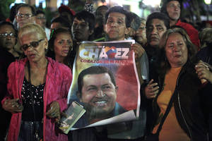 photo - People, one holding an image of Venezuela's President Hugo Chavez, gather to pray for him at Simon Bolivar square in Caracas, Venezuela, Tuesday, Dec. 11, 2012. Doctors began operating on Chavez in Cuba, his government said, after his cancer reappeared despite a year and a half of surgeries and treatments. (AP Photo/Fernando Llano)