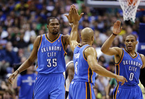 Photo - Oklahoma City Thunder's Kevin Durant (35) celebrates with Derek Fisher (6) and Russell Westbrook (0) during the first half of an NBA basketball game against the Dallas Mavericks, Sunday, March 17, 2013, in Dallas. The Thunder won 107-101. (AP Photo/LM Otero) ORG XMIT: DNA112