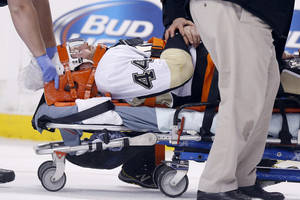 Photo - Pittsburgh Penguins' Brooks Orpik is taken off the ice after being injured in the first period of an NHL hockey game against the Boston Bruins in Boston, Saturday, Dec. 7, 2013. (AP Photo/Michael Dwyer)