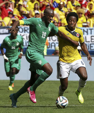 Photo - Ivory Coast's Yaya Toure, left, pushes off Colombia's Carlos Sanchez Moreno to get to the ball during the group C World Cup soccer match between Colombia and Ivory Coast at the Estadio Nacional in Brasilia, Brazil, Thursday, June 19, 2014.  (AP Photo/Martin Mejia)