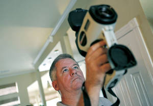 Photo - Dan Ward, a project engineer with Guaranteed Watt Saver, demonstrates how he uses an infrared camera to perform an energy evaluation at a home. Photos by JOHN CLANTON, The Oklahoman