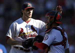Photo - St. Louis Cardinals relief pitcher Kevin Siegrist, left, and catcher Tony Cruz celebrate their 4-0 victory over the Chicago Cubs in a baseball game on Sunday, Sept. 29, 2013, in St. Louis. (AP Photo/Jeff Roberson)