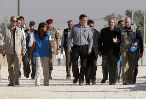 "Photo -   Britain's Prime Minister David Cameron, center, walks with Jordanian Foreign Minister Nasser Judeh, second left, and United Nations High Commissioner for Refugees (UNHCR) representative to Jordan Andrew Harper, right, during his visit to Zaatari refugee camp in Mafraq, Jordan, Wednesday, Nov. 7, 2012. British Prime Minister David Cameron, visiting a camp for Syrian refugees in Jordan, said the U.S., Britain and other allies should do more to ""shape the opposition"" into a coherent force and open channels of communication directly with rebel military commanders. Previously, Britain and the U.S. have acknowledged contacts only with exile groups and political opposition figures inside Syria. (AP Photo)"