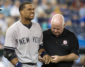 Photo - New York Yankees' Robinson Cano is attended to by trainer Steve Donohue after getting hit on the hand by a pitch from Toronto Blue Jays starting pitcher J.A. Happ during the first inning of a baseball in Toronto on Tuesday, Aug.  27, 2013. (AP Photo/The Canadian Press, Frank Gunn)