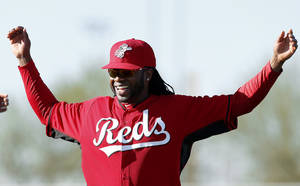 Photo - Cincinnati Reds pitcher Johnny Cueto smiles while stretching during spring training baseball practice in Goodyear, Ariz., Saturday, Feb. 15, 2014. (AP Photo/Paul Sancya)