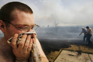 Photo - John Brewer holds a wet towel to his face after battling wild fires in his housing addition in Midwest City  Thursday, April 9, 2009.  Photo by Jim Beckel, The Oklahoman