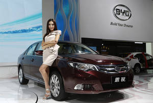 Photo -   In this Thursday, Nov. 22, 2012 photo, a model poses next to a BYD (Build Your Dream) Si Rui at the company's booth during the Guangzhou 2012 Auto Show in China's southern city of Guangzhou. Chinese automaker BYD Company may be hoping that Si Rui, the name for its new midsize sedan, translates into turnaround. The ailing company, which counts billionaire Warren Buffet as an investor, is banking on the new model to help spur a revival in sales. (AP Photo/Vincent Yu)