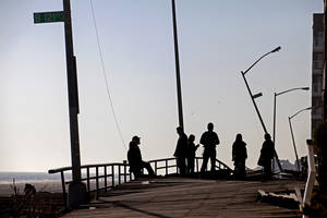 Photo -   People gather on the buckled boardwalk of the Rockaway Park neighborhood of the borough of Queens, New York, Sunday, Nov. 11, 2012, in the wake of Superstorm Sandy. (AP Photo/Craig Ruttle)