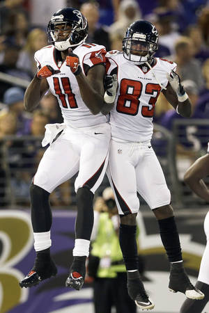 Photo - Atlanta Falcons wide receiver Julio Jones, left, celebrates his touchdown with wide receiver Harry Douglas during the first half of a preseason NFL football game against the Baltimore Ravens in Baltimore, Thursday Aug. 15, 2013. (AP Photo/Patrick Semansky)