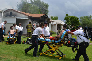 photo - Paramedics attend to two men after a fire broke out Saturday in southwest  Oklahoma City. Photo by Zeke Campfield, the Oklahoman