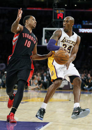 Photo - Los Angeles Lakers' Kobe Bryant, right, passes the ball around Toronto Raptors' DeMar DeRozan, left, during the first quarter of an NBA basketball game in Los Angeles, Sunday, Dec. 8, 2013. (AP Photo/Danny Moloshok)