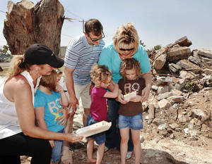Photo - Television reporter Rebecca Cooper, left, watches and listens as Nathan and Amber Kriesel read a greeting card with their daughters, from left,  twins Zoe and Sophie, 4, and Kaley, 6. Amber and Nathan Kriesel and their  three daughters survived the May 20 tornado, but their home at 601 SW 6 in Moore, and most of their possessions, were destroyed or scattered with the winds.  On Saturday, July 13, 2013, the couple brought their daughters to the site where their home once stood.  Nothing remains except dirt and sand. The foundation, driveway and sidewalks are piled about five-feet high next to the curb on 6th Street. Their neighborhood is practically.  Rebecca Cooper, a  reporter from a Washington D.C. television station,  met the Kriesel family   in their former yard to return to them a large manila envelope filled with  sentimental items, including family letters and cards,  and daughter Zoe's artwork, that had been salvaged from the ruins in the days after the twister demolished their home.  Nathan and Amber expressed  gratitude for  special keepsakes  that have been returned in the days and weeks following the storm and since have been returned to them-- Amber's locket, Nathan's high school soccer jacket,  letters and cards dating back decades, from parents, loved ones, friends and grandparents who are now deceased.     Photo  by Jim Beckel, The Oklahoman.