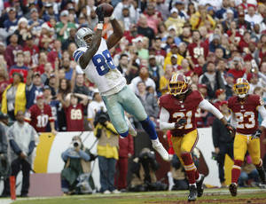 Photo - Dallas Cowboys wide receiver Dez Bryant pulls in a touchdown pass next to Washington Redskins strong safety Brandon Meriweather during the first half of an NFL football game in Landover, Md., Sunday, Dec. 22, 2013. (AP Photo/Alex Brandon)