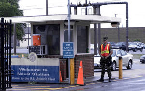 Photo - FILE - In this May 3, 2004 file photo, security personnel wait to inspect vehicles entering Norfolk Naval Station in Norfolk, Va. A sailor was fatally shot at the world's largest naval base late Monday, March 24, 2014, and security forces killed a male civilian suspect, base spokeswoman Terri Davis said. (AP Photo/The Virginian-Pilot, Mort Fryman)