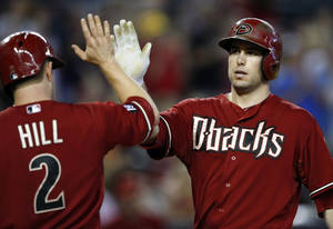 Photo - Arizona Diamondbacks' Paul Goldschmidt, right, celebrates with teammate Aaron Hill (2) in the third inning after hitting a two-run home run during a baseball game against the Colorado Rockies, Sunday, Sept. 15, 2013, in Phoenix. (AP Photo/Rick Scuteri)