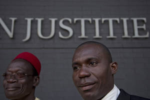 photo -   Alali Efanga, right, and Chief Fidelis A. Oguru, plaintiffs in the court case of Nigerian farmers against Shell, wait for the start of their case in The Hague, Netherlands, Thursday Oct. 11, 2012. Nigerian farmers are suing Shell in a Dutch court, asking judges to order the oil multinational to clean up environmental damage the farmers say is caused by leaking pipes. Thursday's case in The Hague Civil Court is a legal landmark in the Netherlands as it marks the first time a Dutch company has been sued for alleged environmental mismanagement caused by an overseas subsidiary. (AP Photo/Peter Dejong)