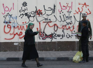"photo - A woman walks past Arabic writings on a wall that read, ""no, leave, Muslim Brotherhood,"" in front of the presidential palace in Cairo, Egypt, Thursday, Dec. 13, 2012. Egypt's opposition called on its followers to vote ""no"" in a crucial referendum on a disputed constitution drafted by Islamist supporters of President Mohammed Morsi. (AP Photo/Hassan Ammar)"