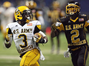 Photo - West player Trey Williams, left, is chased by East player Deon Bush during the fourth quarter of the U.S. Army All-American Bowl in San Antonio, Texas, Saturday Jan. 7, 2012. (AP Photo/Delcia Lopez) ORG XMIT: TXDL107