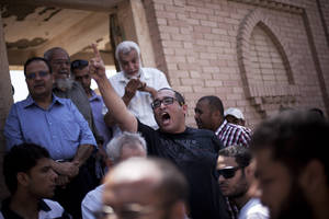 """Photo - A friend of Ammar Badie, 38, killed Friday by Egyptian security forces during clashes in Ramses Square, and also son of Muslim Brotherhood's spiritual leader Mohammed Badie, shouts, """"Allah is the greatest,"""" while attending his burial in Cairo's Katameya district, Egypt, Sunday, Aug. 18, 2013. Egypt increased security at the Supreme Constitutional Court building ahead of planned mass rallies by supporters of the country's ousted President Mohammed Morsi. (AP Photo/Manu Brabo)"""