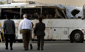 photo - National Transportation Safety Board members walk toward the bus crash site Tuesday, Feb. 5, 2013, in Ontario, Calif., before giving an update on the investigation of Sunday's tour bus crash near Yucaipa that killed seven people.(AP Photo/.Inland Valley Daily Bulletin, Jennifer Cappuccio Maher)