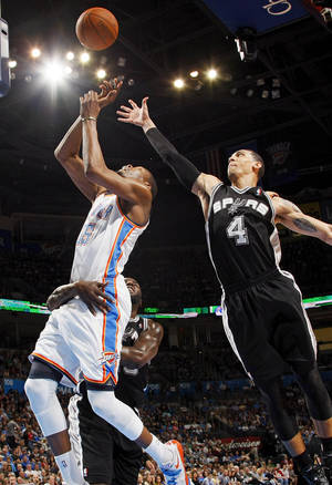 photo - Oklahoma City's Kevin Durant, left, is fouled by San Antonio's DeJuan Blair, back, as Danny Green defends at Chesapeake Energy Arena on Friday.  Photo by Nate Billings, The Oklahoman