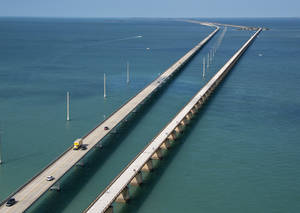 Photo - This aerial photo provided by the Florida Keys News Bureau shows the historic Seven Mile Bridge, right, in the Florida Keys near Marathon, Fla., Wednesday, March 19, 2014. The Monroe County Commission Wednesday ratified an agreement between the Florida Department of Transportation, the City of Marathon and the county to begin a 30-year, $77 million restoration and maintenance program on a 2.2-mile segment of the century-old span between Marathon and Pigeon Key. The bridge that once supported Henry Flagler's Florida Keys OverSea Railroad was retired in 1982, after the new span, left, opened to traffic. (AP Photo/Florida Keys News Bureau, Andy Newman)