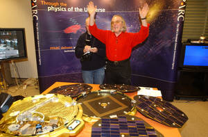 Photo - FILE - A Thursday, Dec. 25, 2003 photo from files of Professor Colin Pillinger, leading scientist for the Beagle 2 Mars landing module, gestures in a control centre in central London in front of a model of the 'pod' which landed on Mars as he waits for radio signals from the device. Pillinger, an ebullient British space scientist who captured the popular imagination with his failed attempt to land a probe on Mars, has died. He was 70. Pillinger's family said Thursday that he died at Addenbrooke's Hospital in Cambridge after suffering a brain hemorrhage while sitting in his garden in the university town. (AP Photo/Adam Butler)