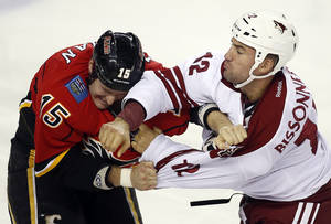 Photo - Phoenix Coyotes' Paul Bissonnette, right, fights with Calgary Flames' Tim Jackman during the third period of an NHL preseason hockey game, Wednesday, Sept. 25, 2013, in Calgary, Alberta. The Coyotes won 3-2. (AP Photo/The Canadian Press, Jeff McIntosh)