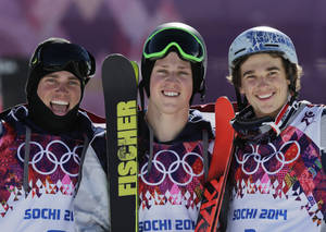 Photo - Men's ski slopestyle gold medal winner Joss Christensen of the United States, center, celebrates on the podium with his teammates Gus Kenworthy, left, silver, and Nicholas Goepper, bronze, right, during a flower ceremony at the Rosa Khutor Extreme Park, at the 2014 Winter Olympics, Thursday, Feb. 13, 2014, in Krasnaya Polyana, Russia.  (AP Photo/Andy Wong)