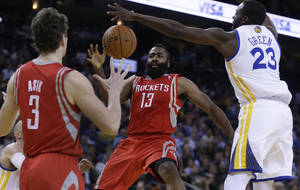 Photo - Houston Rockets' James Harden (13) passes away from Golden State Warriors' Draymond Green (23) to Omer Asik (3) during the second half of an NBA basketball game Thursday, Feb. 20, 2014, in Oakland, Calif. (AP Photo/Ben Margot)
