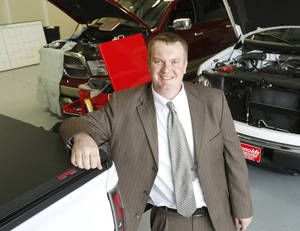 Photo - CNG Interstate owner Craig Wright stands in front of several vehicles being converted to CNG at his business in Oklahoma City.