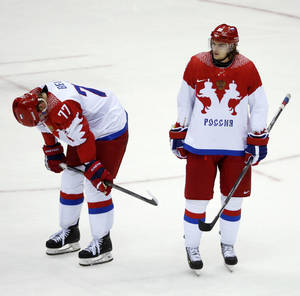 Photo - Russia defenseman Anton Belov and Russia forward Viktor Tikhonov react at the end of a men's quarterfinal ice hockey game against Finland at the 2014 Winter Olympics, Wednesday, Feb. 19, 2014, in Sochi, Russia. Finland won 3-1. (AP Photo/Mark Humphrey)