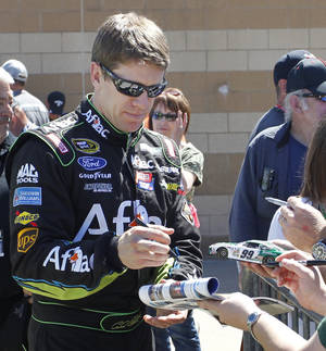 Photo - Driver Carl Edwards signs autographs  Friday, May 9, 2014, at Kansas Speedway in Kansas City, Kan., for Saturday night's NASCAR Sprint Cup series auto race. (AP Photo/Colin E. Braley)