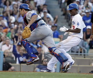 Photo -   Los Angeles Dodgers' Dee Gordon, right, scores on an error by New York Mets catcher Mike Nickeas, left in the seventh inning of a baseball game in Los Angeles on Sunday, July 1, 2012. (AP Photo/Christine Cotter)