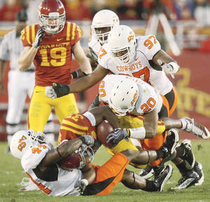 Photo - OSU's Donald Booker, left, Andre Sexton, and Jermiah Price bring down Iowa State's Alexander Robinson during the Cowboys' 34-0 win over Iowa State. Price said OSU emphasized stopping the run in preparation for the Cyclones.  PHOTO BY BRYAN TERRY, THE OKLAHOMAN