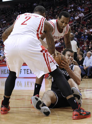 Photo - Brooklyn Nets' Kris Humphries struggles for the ball between Houston Rockets' Marcus Morris (2) and Greg Smith, rear, in the first half of an NBA basketball game Saturday, Jan. 26, 2013, in Houston. (AP Photo/Pat Sullivan)