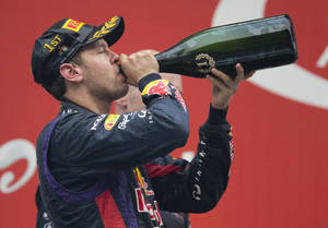 Photo - Red Bull driver Sebastian Vettel of Germany -drinks champagne after winning the Indian Formula One Grand Prix and his 4th straight F1 world drivers championship at the Buddh International Circuit in Noida, India, Sunday, Oct. 27, 2013. (AP Photo/Mark Baker)