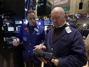 Photo - FILE - In this Wednesday, Jan. 8, 2014, file photo, specialist Jason Hardzewicz, left, and trader John Doyle work on the floor of the New York Stock Exchange. Stock indexes are slightly higher in early trading Friday, Jan. 10, 2014. (AP Photo/Richard Drew, File)