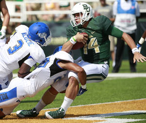 Photo - Baylor quarterback Bryce Petty, right, scores past Buffalo defensive back Okezie Alozie (3) and Adam Redden (29) in the first half of a NCAA college football game, Saturday, Sept., 7, 2013, in Waco, Texas. (AP Photo/Waco Tribune Herald, Jose Yau)