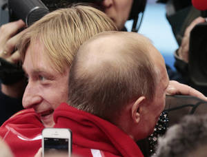 Photo - Russian President Vladimir Putin, right, embraces Evgeni Plushenko after Russia placed first in the team figure skating competition at the Iceberg Skating Palace during the 2014 Winter Olympics, Sunday, Feb. 9, 2014, in Sochi, Russia. (AP Photo/Ivan Sekretarev)