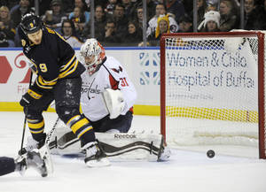 Photo - Buffalo Sabres center Steve Ott (9) deflects the puck wide of Washington Capitals goaltender Philipp Grubauer (31), of Germany, during the first period of an NHL hockey game in Buffalo, N.Y., Sunday, Dec. 29, 2013. (AP Photo/Gary Wiepert)