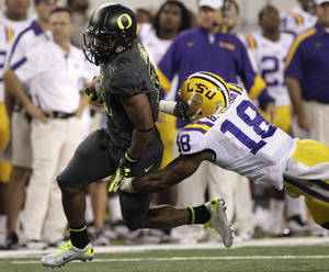 Photo - Oregon running back LaMichael James, left, attempts to escape a tackle by LSU's Brandon Taylor (18) in the first half of the Cowboys Classic NCAA college football game Saturday, Sept. 3, 2011, in Arlington, Texas. (AP Photo/Tony Gutierrez) ORG XMIT: CBS126