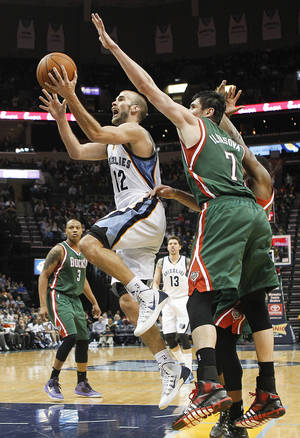 Photo - Memphis Grizzlies guard Nick Calathes (12) drives to the basket against Milwaukee Bucks forward Ersan Ilyasova (7), of Turkey, in the second half of an NBA basketball game on Saturday, Feb. 1, 2014, in Memphis, Tenn. The Grizzlies won 99-90. (AP Photo/Lance Murphey)