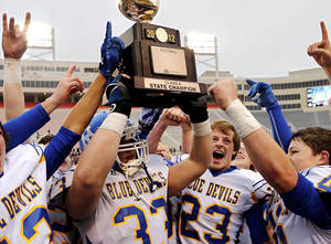 photo - Ringling players celebrate with the championship trophy. #33 is Allen Patrick. #23 is Joe Hill. Ringling Blue Devils defeated Wynnewood, Savages 39-12  in the  Class A High School football championship game at Boone Pickens Stadium in Stillwater on Saturday,  Dec. 8, 2012.  Photo by Jim Beckel, The Oklahoman