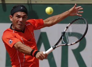 Photo - Dominican Republic's Victor Estrella Burgos backhands to Poland's Jerzy Janowicz during their first round match of  the French Open tennis tournament at the Roland Garros stadium, in Paris, France, Sunday, May 25, 2014. (AP Photo/Michel Euler)