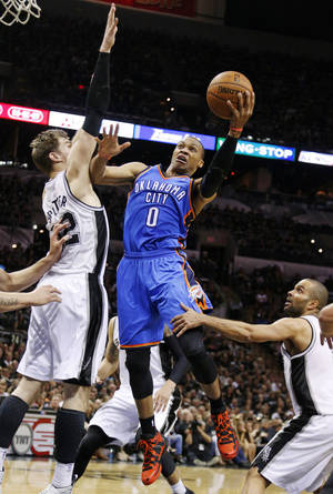 Photo - Oklahoma City's Russell Westbrook (0) takes the ball to the basket between San Antonio's Tiago Splitter (22) and Tony Parker (9) during Game 1 of the Western Conference Finals in the NBA playoffs between the Oklahoma City Thunder and the San Antonio Spurs at the AT&T Center in San Antonio, Monday, May 19, 2014. Photo by Sarah Phipps, The Oklahoman